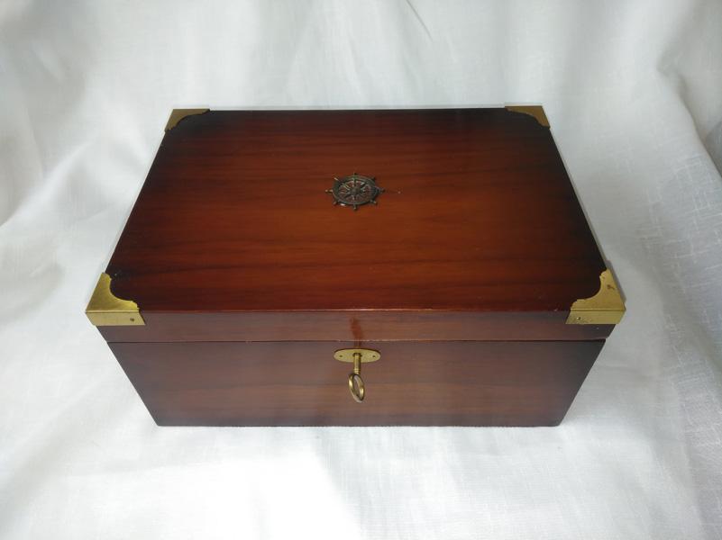 Caja chapeada en nogal con herrajes de latón y motivos nauticos.